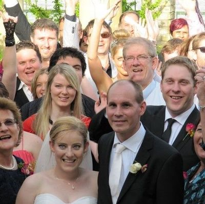 Image of bride and groom surrounded by family and friends posing for photo after wedding ceremony.