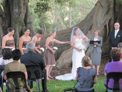 Image of bridesmaids and bride laughing with celebrant and groom during ceremony