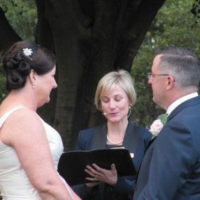 Image of bride and groom   standing holding hands with celebrant reading between them during wedding ceremony.