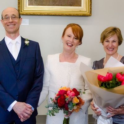 Image of bride, groom and celebrant smiling for photographer after ceremony.