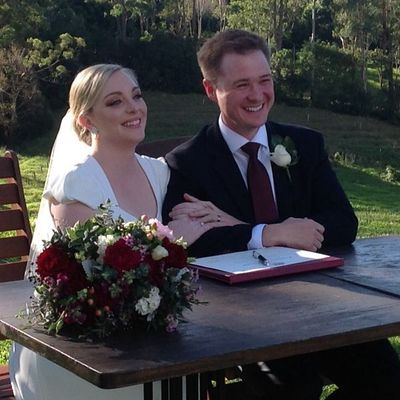 Image of bride and groom posing for photos at wedding signing table