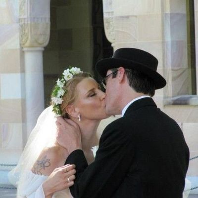 Image of happy bride and groom sharing first kiss during wedding ceremony.