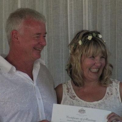 Image of the happy bride and groom with their wedding certificate during ceremony.