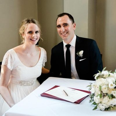 Image of bride and groom sitting at signing table during wedding ceremony and smiling for  photographer.