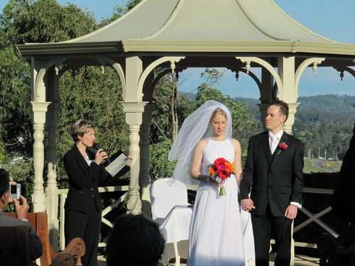 Image of celebrant speaking as bride and groom hold hands during wedding ceremony