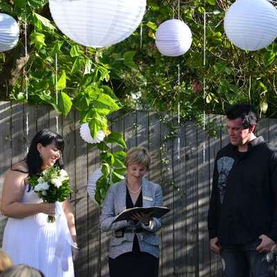 Image of bride and groom standing on either side of celebrant during wedding in their back yard.